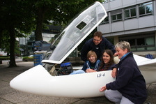 Prospective students examining a glider (airplane) at a University Open Day